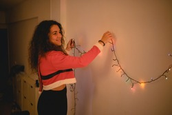 Girl dressed on a Santa Claus costume decorates her living room putting christmas color lights on it