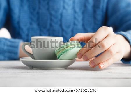 Girl drink coffee and hold macaroon #571623136