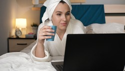 Girl drinking coffee or tea and working on laptop. Attractive woman in bedroom in white bathrobe lies in bed drinks hot coffee or tea and uses laptop. Close-up view