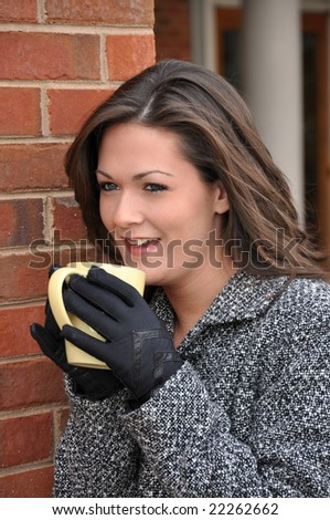 Girl drinking coffee outside with coat on.