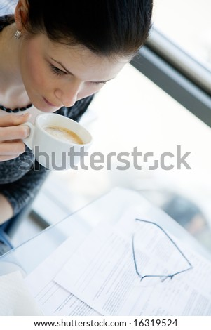 Girl drinking coffee with her eyeglasses and papers putting aside