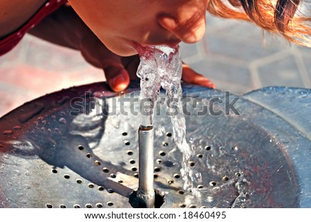 Girl drinking on water fountain outdoor
