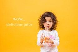 Girl drinking orange juice on an isolated yellow background, place for your text
