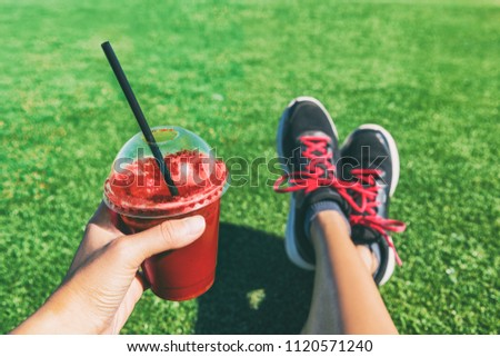 Girl drinking red beet or fruit smoothie plastic cup during fitness workout. Healthy detox juice woman holding drink shower running shoes in food selfie photo. Sport active lifestyle