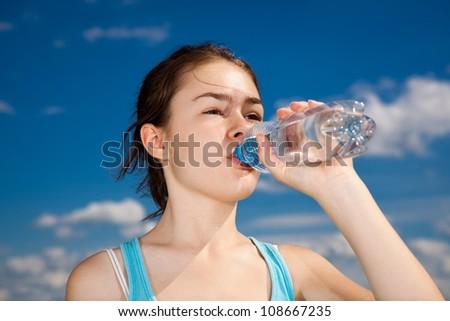 Girl drinking water against blue sky