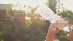Girl drinking water of bottle on hot day preventing heat ,prevent heatstroke
