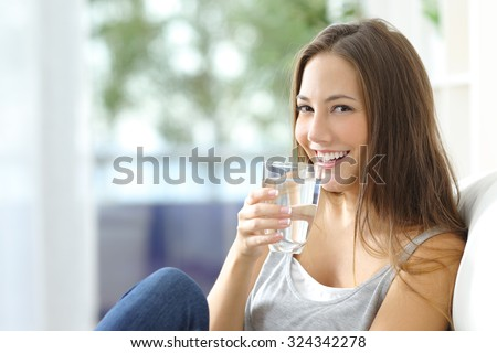 Girl drinking water sitting on a couch at home and looking at camera