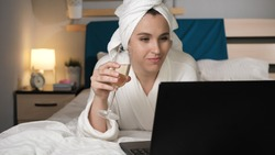 Girl drinking wine and working on laptop. Attractive woman in bedroom in white bathrobe lies in bed drinks champagne and uses laptop. Close-up view