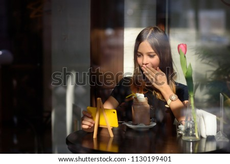 girl drinks coffee and watches video on mobile phone #1130199401