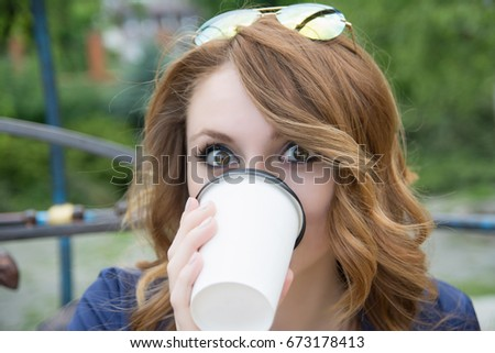 Girl drinks coffee outdoors in the park #673178413