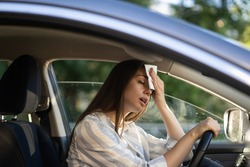 Girl driver being hot during heat wave in car, suffering from hot weather, has problem with a non-working air conditioner, wipes sweat from her forehead with tissue. Summer, heat concept.