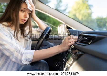 Girl driver has problem with a non-working conditioner, hand checking flow cold air, being hot during heat wave in car, suffering from summer hot weather, wipes sweat from her forehead with tissue.  Foto stock ©