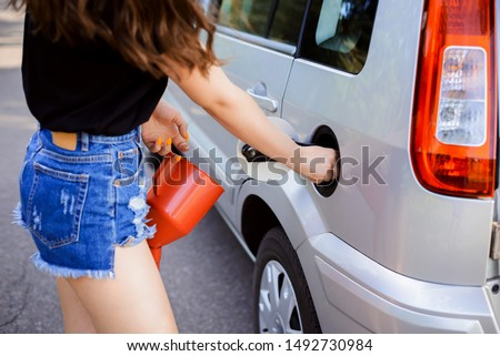 Girl driver opens car fuel tunk before filling it using jerrican #1492730984