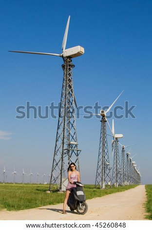 Girl driving bicycle on the road in wind farm.
