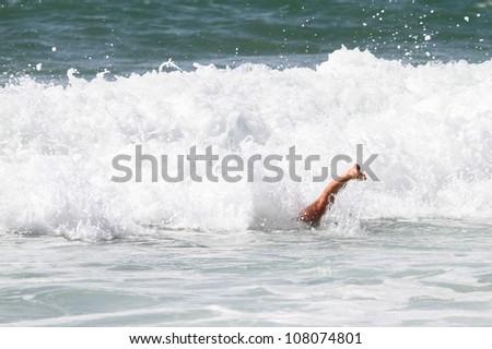 girl duck diving under wave