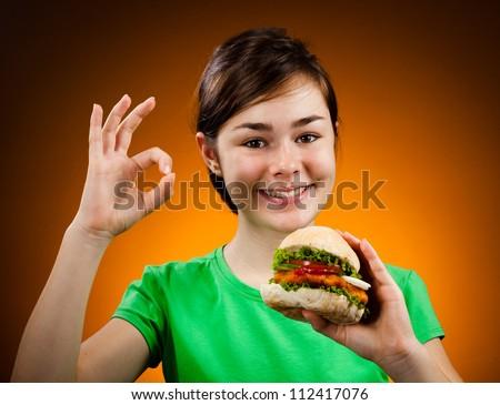 Girl eating big sandwich showing OK sign