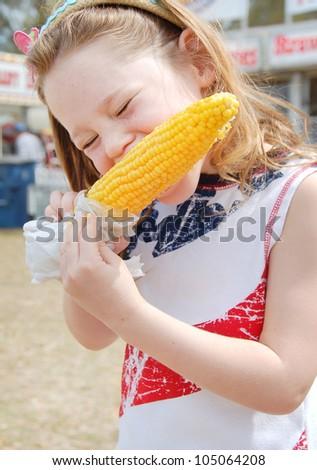 Girl eating corn at fair