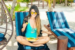 girl eating fruits on a deck chair on the beach, holbox, mexico