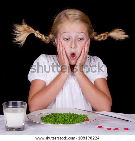 girl eating peas with bugs on the table isolated on black