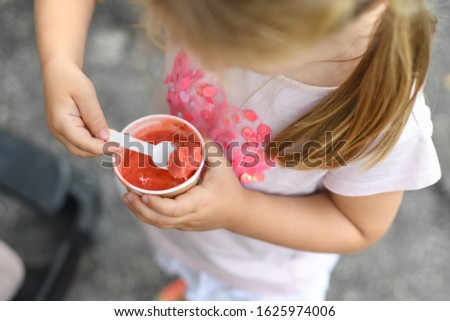 Girl eats pink ice cream. View from above
