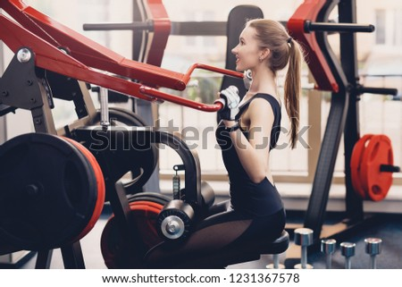 Girl engaged the training apparatus for the backs. A happy young girl performs a physical exercise on a training apparatus the strength of the muscles of the back. Training on the training apparatus