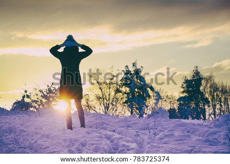 Stock Photo girl enjoying a sunset during a walk in winter landscape, beautiful snow-covered countryside. woman wearing black coat and winter hat.