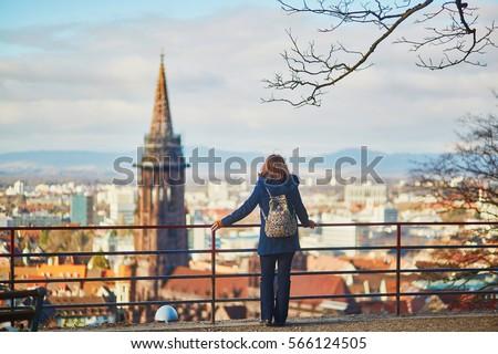 Girl enjoying beautiful panorama of Freiburg im Breisgau in Germany #566124505