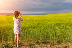 Girl enjoying green wheat field in countryside. Field of wheat blowing in the wind at sunny spring day. Young and green Spikelets. Ears of barley crop in nature. Agronomy, industry and food production
