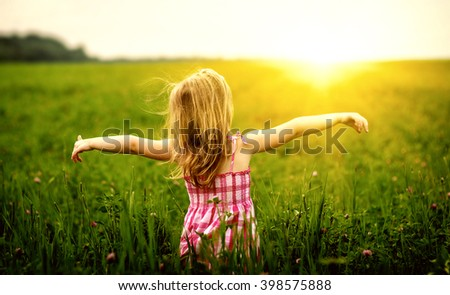 Girl enjoying nature in meadow. Outstretched arms fresh morning air summer field at sunrise