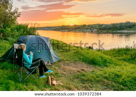 Girl enjoying the sunset in camping near the river #1039372384