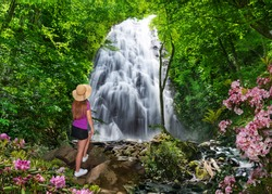 Girl enjoying waterfall in in the forest on summer vacation trip. Crabtree Falls with blooming flowers  just off the Blue Ridge Parkway. Blue Ridge Mountains, North Carolina, USA.