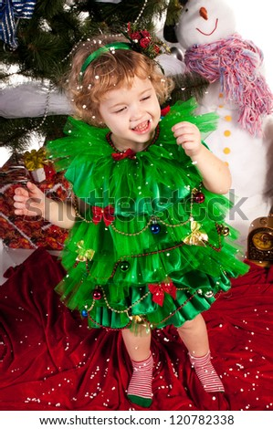Girl enjoys the snow and catch it with his hands, a Christmas tree, studio photography