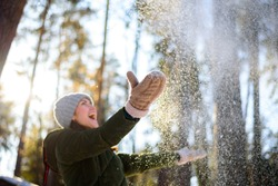 Girl enjoys winter, frosty day, snow. playing with snow, a woman throws white, loose snow into the air. Walk with winter forest.