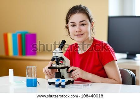 Girl examining preparation under the microscope