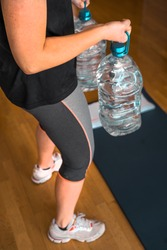 girl exercising lifting five liters water bottles in her home living room