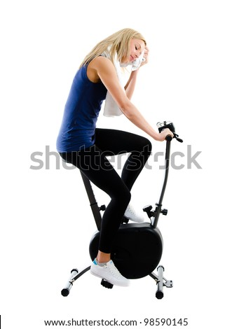 Girl exercising on stationary training bicycle and drying her face with towel