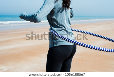 Girl exercising with hula hoop on the beach close up #1056188567
