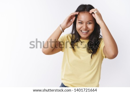Girl expressing positive vibes with good mood, checking haircut while dancing smiling broadly from happiness and joy, moving music rhythm having fun and enjoying awesome company over white wall #1401721664
