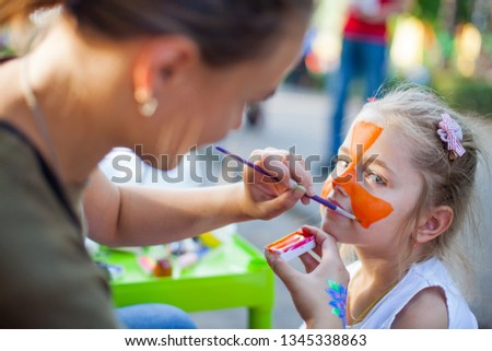 Girl face close-up with red colors on his face, face painting watercolor, artist paints watercolor paints tiger mask, draw on the girl's face paints picture, orange ink for drawing the tiger.