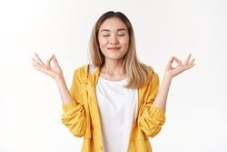Girl feel relaxed joyful calm. Attractive peaceful asian blonde student gather courage patience breath air close eyes smiling delighted hold hands zen mudra gesture nirvana meditation, practice yoga