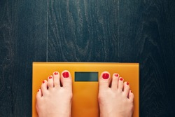 Girl feet with red toes on electric scales on wooden background. Diet concept