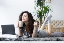Girl female woman wearing pajamas sleepwear with white hearts lying on the carpet in light interior room and smelling aroma of cup of coffee tea and working with laptop. Freelancer, working at home.