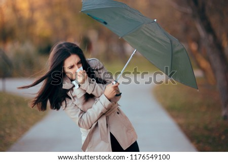Girl Fighting The Wind Holding Umbrella Raining Weather. Autumn woman having problems in windy storm