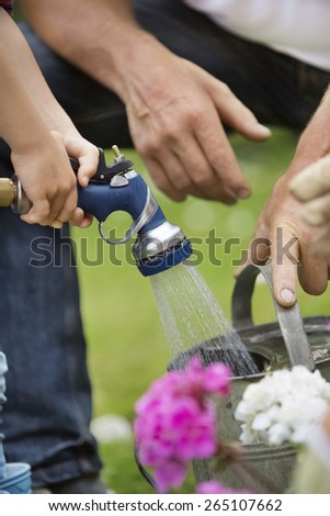 Girl filling watering can with garden hose