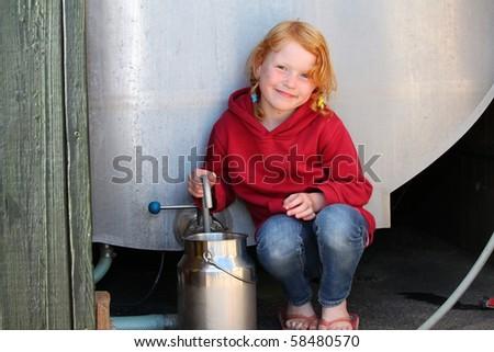 Girl fills milkcan from milk tank