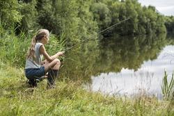 girl fishing at lake in summer vacation