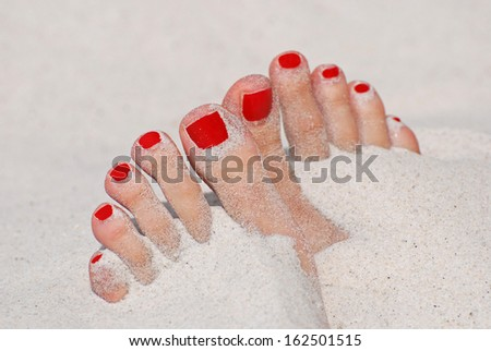 Girl foot in sand on the beach - red nails