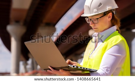 Girl foreman with laptop at construction site. female engineer works on computer under overpass under construction.
