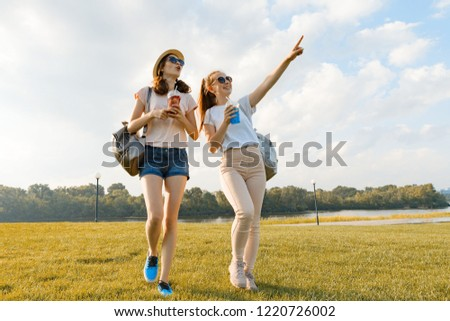 Girl friends are walking in the park in nature. Girls walk along the green lawn, talk, have fun. #1220726002