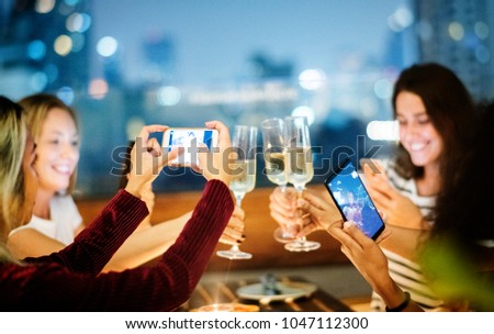 Girl friends having a dinner together at a rooftop bar taking a photo of the toast social media concept #1047112300